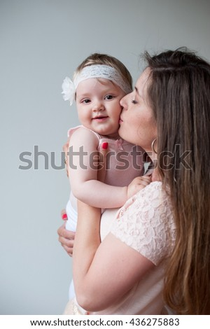 Family, child and parenthood concept - happy mother kissing her smiling baby