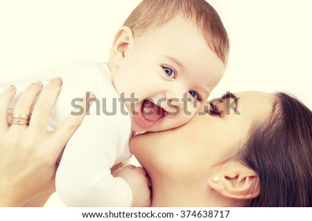 family, child and parenthood concept - happy mother kissing smiling baby
