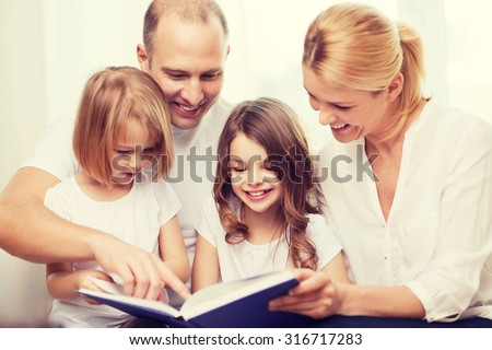 family, children and home concept - smiling family and two little girls with book at home