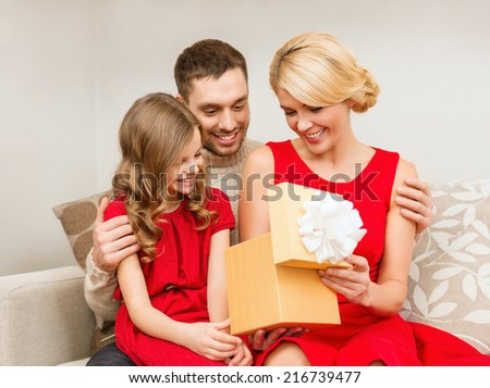 family, christmas, happiness and people concept - happy family opening gift box