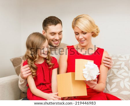 family, christmas, x-mas, winter, happiness and people concept - happy family opening gift box