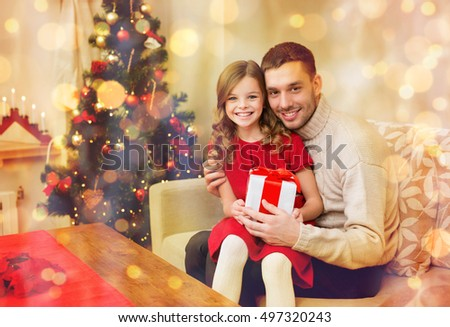 family, christmas, xmas, happiness and people concept - smiling father and daughter holding gift box