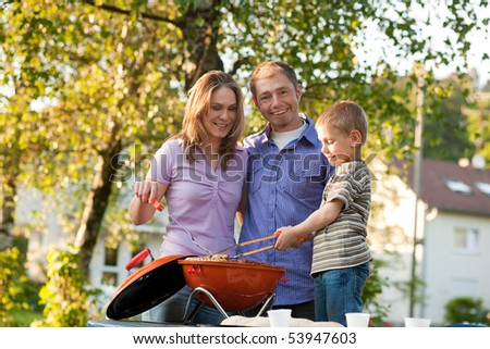 Family - father and son - having a barbecue party, the child is very concentrated on doing the cooking work