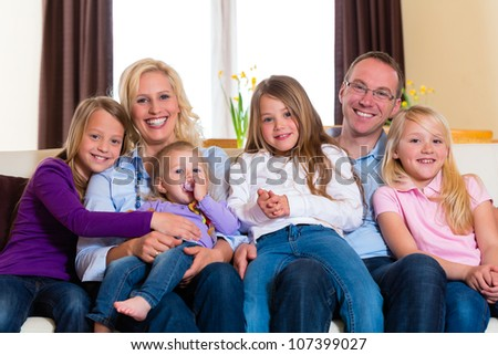 Family, father, mother and four sisters sitting on a couch in their living room