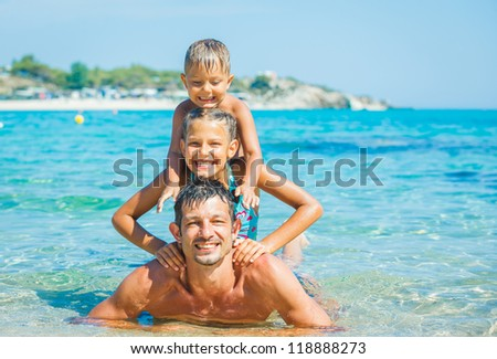 Family - father with his kids have fun and swimming in the transparent sea