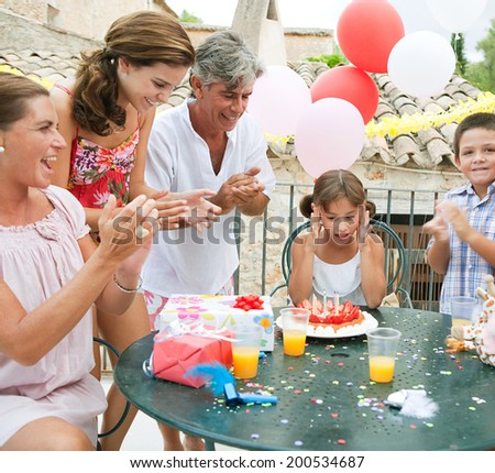 Family group enjoying and celebrating a young girl child birthday during a summer day, sitting around a table with a birthday cake and gifts and a surprised birthday girl. Family celebrating outdoors.