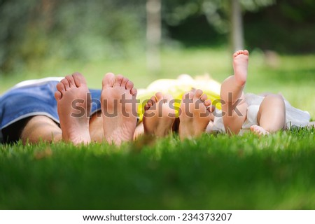 family laying on grass in park