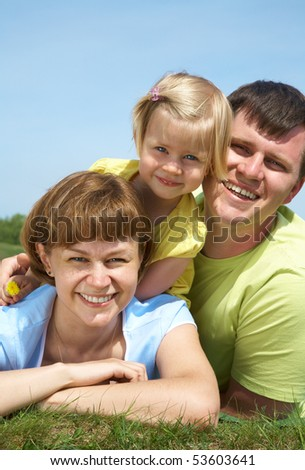 family lifestyle portrait of a mum and dad with their daughter having good time on the green grass
