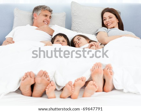 Family lying down in their bed at home
