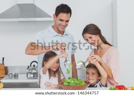 Family mixing a salad together in the kitchen