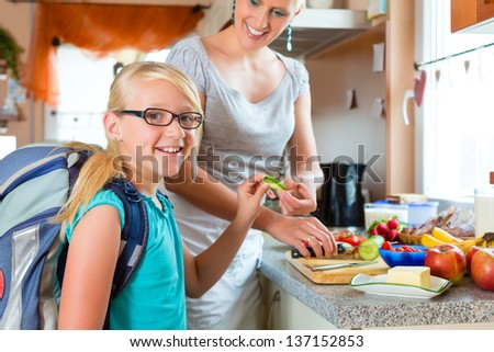 Family - mother making breakfast for her children in the morning and a snack for school