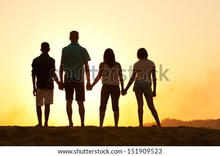 Family of four silhouette by a sunset