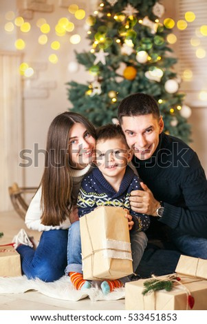 Family of mother, father and little child near Christmas tree with presents, decorations and New Year or Christmas