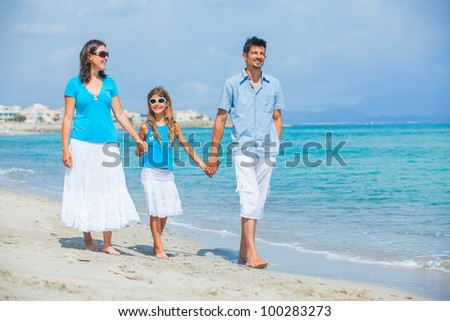 Family of three having fun on tropical beach