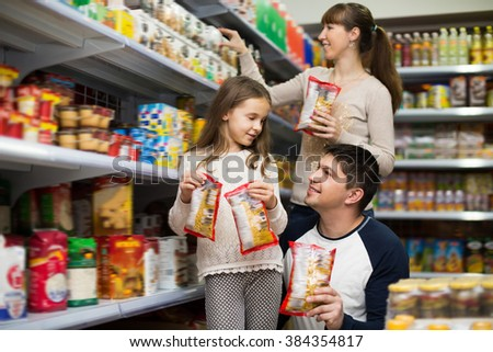 Family of three purchasing food for week at supermarket. Focus on man