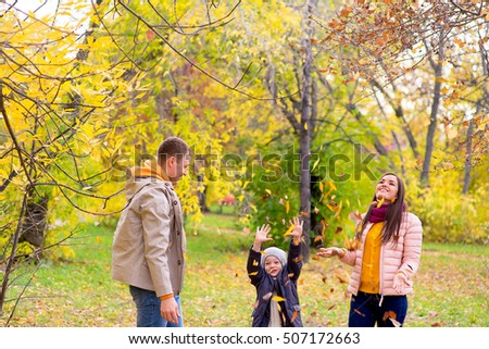 family playing with leaves autumn park between trees, smiling together