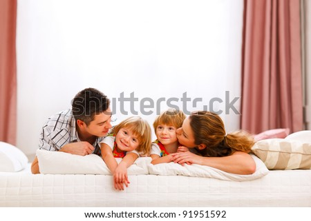 Family portrait of mom dad and twins daughters on bed