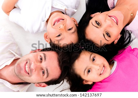 Family portrait with heads together lying on the floor