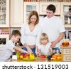 Family Preparing Salad In  Kitchen - stock photo