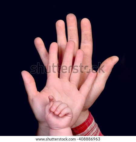 Family reunion concept. Hands of baby, mother and a father, on black background.
