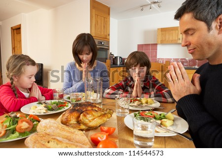 Family Saying Grace Before Eating Lunch Together In Kitchen