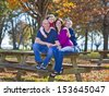 Family sitting on bench during the fall  - stock photo