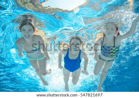 Family swims in pool under water, happy active mother and children have fun, fitness and sport with kids on summer vacation