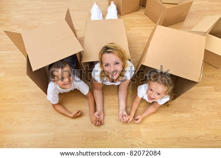 Family unpacking in a new home having fun on the floor