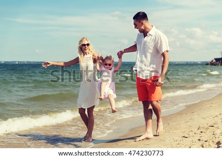 family, vacation, adoption and people concept - happy man, woman and little girl in sunglasses walking and having fun on summer beach