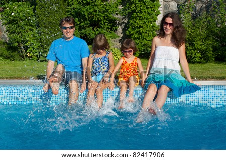 Family vacation. Parents with two kids having fun near swimming pool
