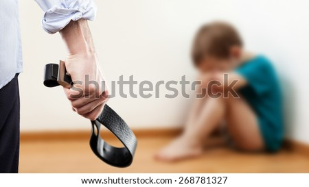 Family violence and aggression concept - furious angry man raised punishment hand holding leather belt over scared or terrified child boy sitting at wall corner