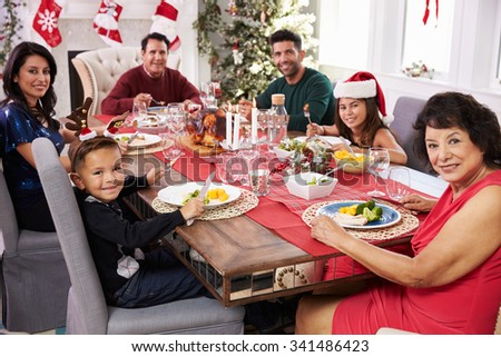 Family With Grandparents Enjoying Christmas Meal At Table