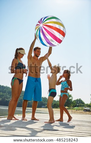 Family with kids and a beach ball at a lake in summer