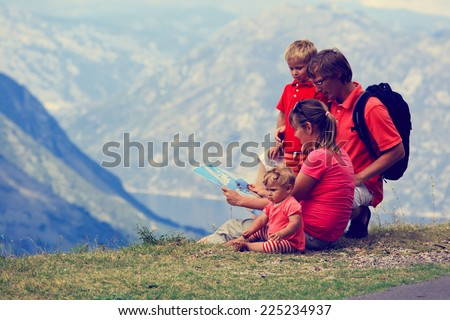 family with kids looking at map in mountains