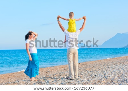 family with son playing on the beach near the sea
