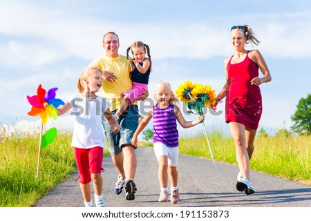Family with three kids running down a hill in summer