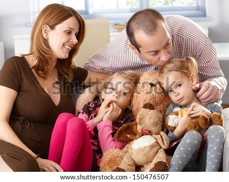 Family with two daughters and pregnant mother sitting on sofa at home, father kissing daughter.