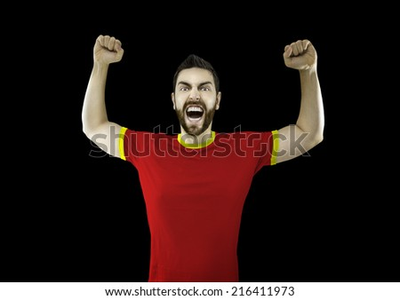 Fan in red and yellow t-shirt celebrates on black background