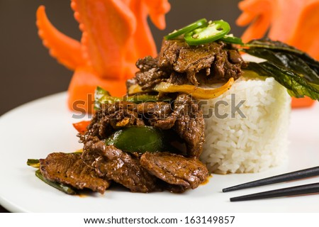 Fancy sliced Asian pepper steak served with white rice and garnished with carved carrot swans on a white plate.
