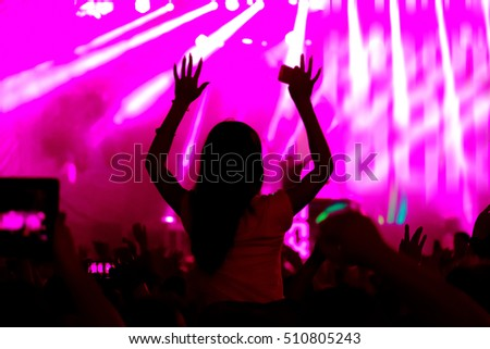 Fans cheering at open-air live concert. Image not in focus