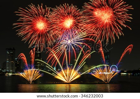Fantastic fireworks over the river with cityscape at night scene background
