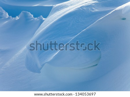 Fantastic texture of snow drifts was created by strong wind.