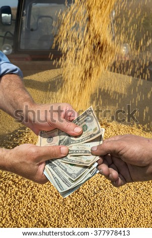 Farmer and buyer hands holding dollar banknote with soy bean crop in background