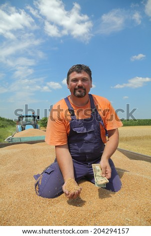 Farmer  holding dollar banknote at wheat crop