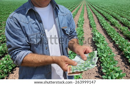 Farmer holding Euro banknote with green cultivated soy field in background