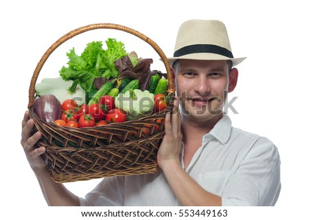farmer in a hat and white shirt carries on his shoulder a basket of vegetables