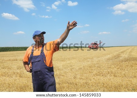 Farmer in wheat field with combine harvester in background