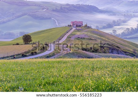 Farmhouse on a hill in a valley in the predawn light