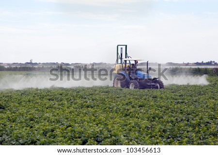 Farming tractor spraying on field