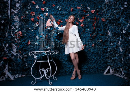 Fashion and beautiful young woman in a green wall of flowers and leaves